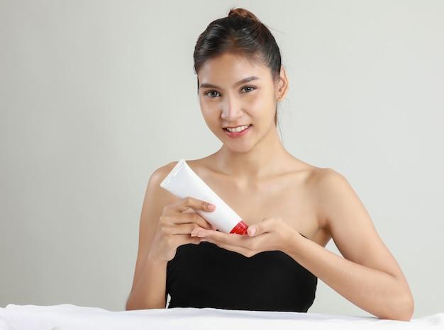 保湿剤のチューブを保持しているアジアの若い女性 無料写真