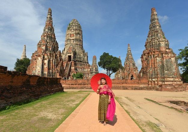 Счастливая пенсионерка в традиционном тайском платье путешествует в храме. Бесплатные Фотографии