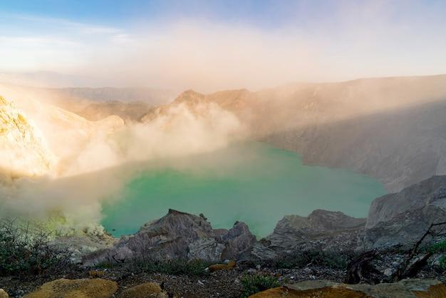 煙を吐き出す岩の多い風景の中にある湖 無料写真