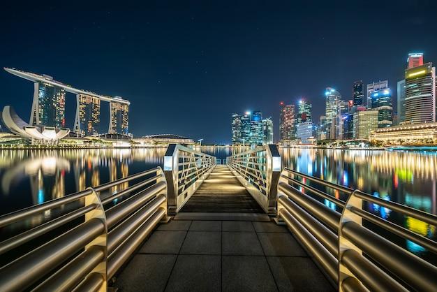 Длинный мост между освещенным городом ночью Бесплатные Фотографии