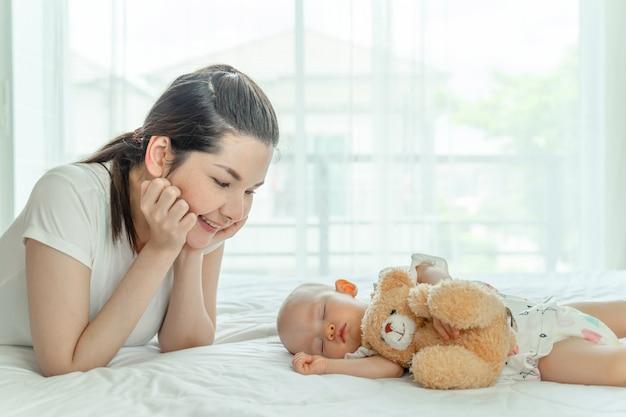 テディベアとそれらを見て母親と一緒に寝ている赤ちゃん 無料写真