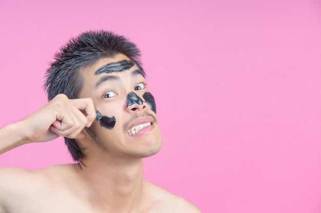 Молодой человек, используя его руки, чтобы удалить черную косметику на лице с болью на розовый. Бесплатные Фотографии