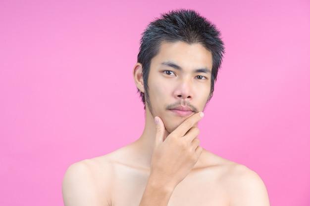 Молодой человек, показывая лицо без макияжа на розовый. Бесплатные Фотографии