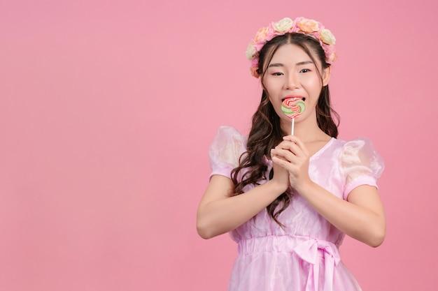 Красивая женщина в розовой принцессе играет со своей сладкой конфеткой на розовом. Бесплатные Фотографии