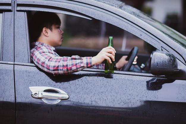 アジア人は車を運転中にビール瓶を保持します 無料写真