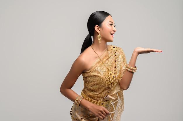 Красивая тайская женщина носит тайскую одежду и раскрывает руку влево Бесплатные Фотографии