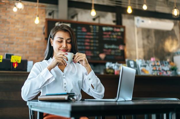 Женщина сидит счастливо пьет кофе в кафе-магазине и ноутбук Бесплатные Фотографии