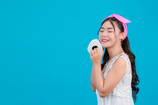 Девушка в белой пижаме, держа в руке рулонной бумаги на синий. Бесплатные Фотографии