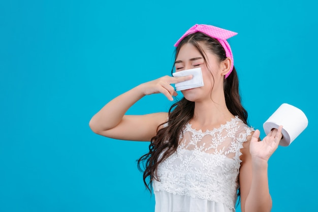 白いパジャマを着ている少女は快適ではありません。ティッシュを使って鼻を青で拭きます。 無料写真