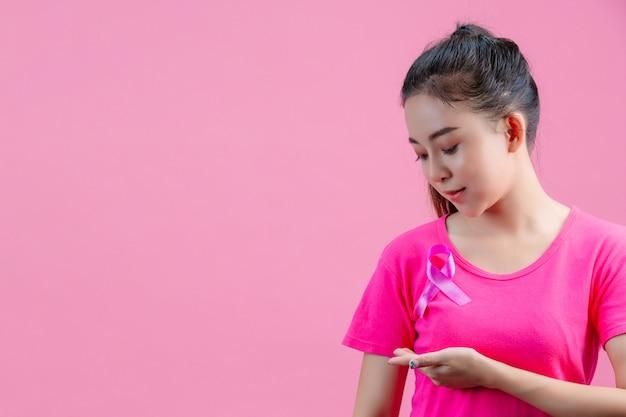 Осведомленность о раке молочной железы, женщина в розовой футболке с атласной розовой лентой на груди, поддерживающая осведомленность о раке молочной железы Бесплатные Фотографии