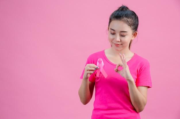 乳がんの意識、ピンクのシャツを着た女性、右手でピンクのリボンを保持左手は大丈夫、乳がんに対する毎日のシンボルを示す 無料写真