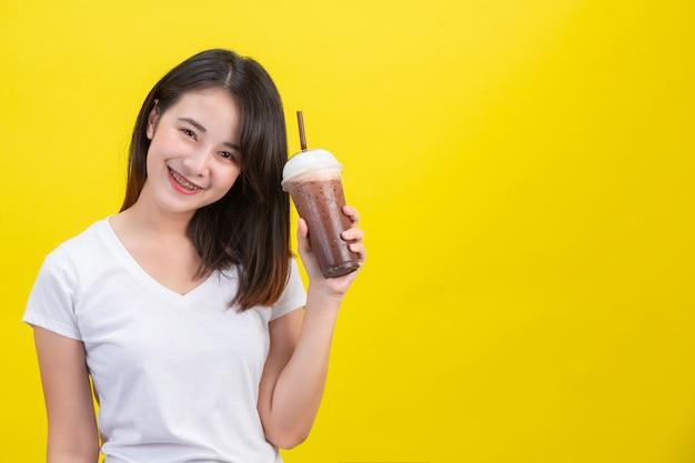 女の子は黄色の透明なプラスチックガラスからココアの冷たい水を飲みます。 無料写真