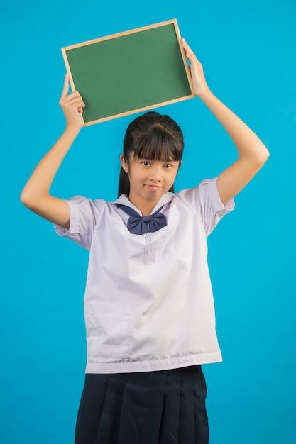 Азиатский студент при длинная девушка волос держа зеленую доску на сини. Бесплатные Фотографии