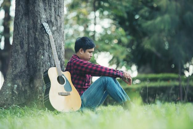 公園でアコースティックギターを持つアジア人 無料写真