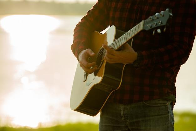 日没時にアコースティックギターを持つアジア人 無料写真