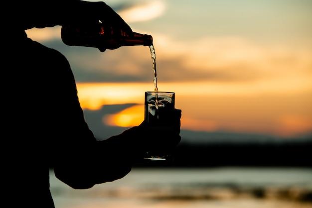 Человек силуэт держит пиво во время заката Бесплатные Фотографии