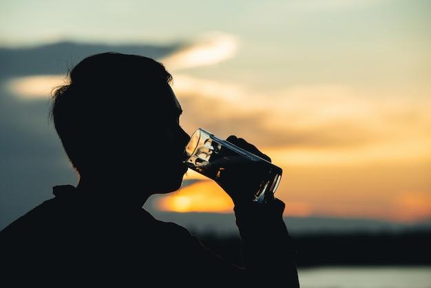 Человек силуэт пьет пиво во время заката Бесплатные Фотографии