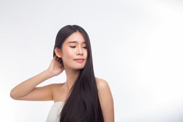 Женщина в белых топах без бретелек и руки касаются ее волос Бесплатные Фотографии