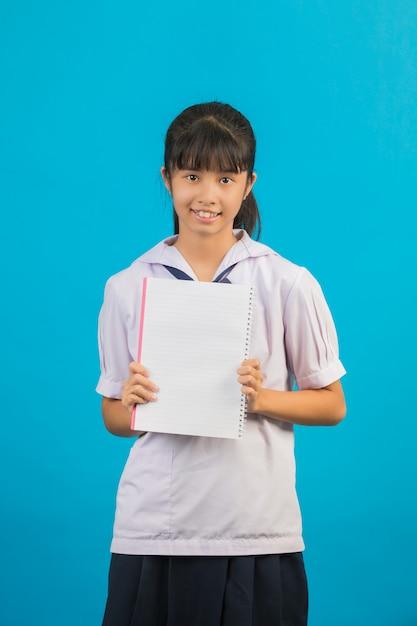 Азиатский студент при длинная девушка волос держа тетрадь на сини. Бесплатные Фотографии