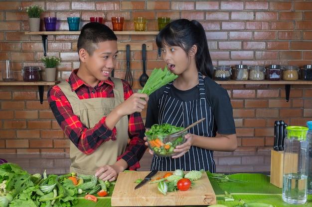 赤レンガの壁でキッチンで料理をしている間、お互いをからかうティーン、カップル、女の子。 無料写真