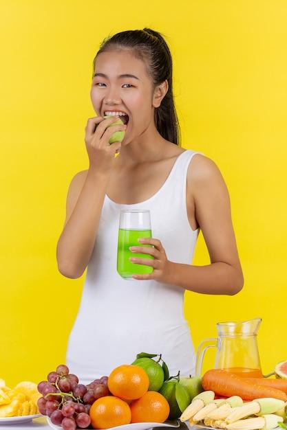 アジアの女性が青リンゴを食べようとしています。リンゴジュースを一杯持ってください。 無料写真