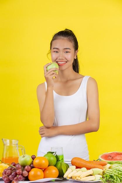緑のリンゴを右手で持っているアジアの女性。テーブルの上にはたくさんの果物があります。 無料写真