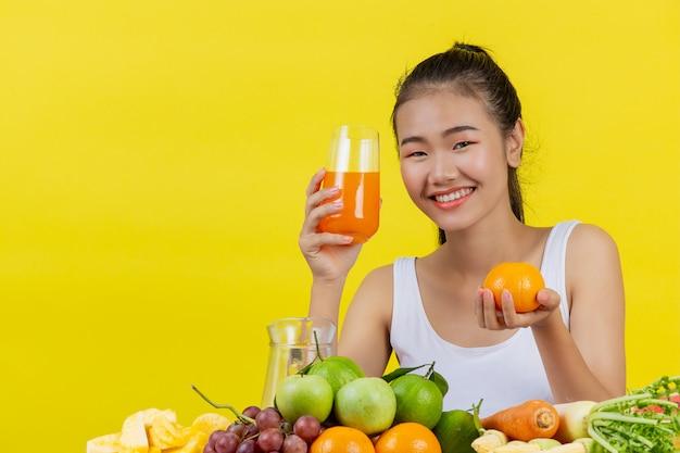 白いタンクトップを着ているアジアの女性。オレンジジュースのグラスを右手で持って左手はオレンジ色を持ち、テーブルにはたくさんの果物がありました。 無料写真