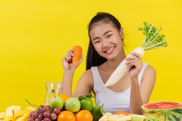 アジアの女性右手でニンジンを握る左手で大根を握ると、テーブルの上にたくさんの果物があります。 無料写真