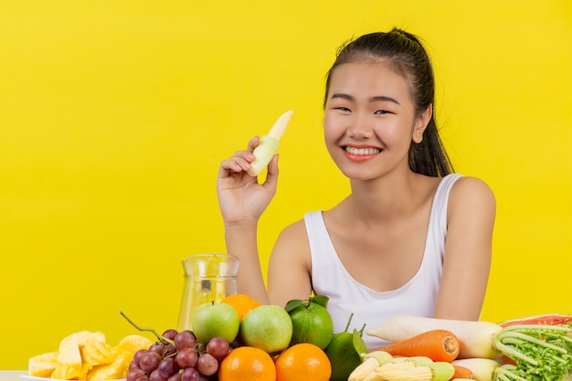白いタンクトップを着ているアジアの女性。ベビーコーンを右手で持ってください。また、テーブルにはさまざまな果物があります。 無料写真