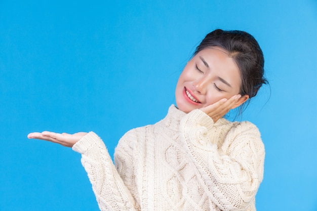 Красивая женщина, носить новый с длинными рукавами белый ковер, показывая жест на синем. торговая Бесплатные Фотографии