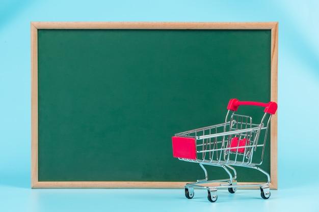 オンラインショッピング、青い緑色のボードに置かれたダブルカート。 無料写真