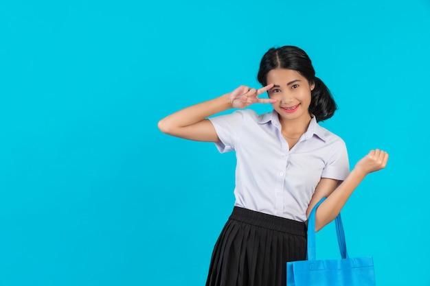 アジアの女子学生が布の袋を回転させて、青色でさまざまなジェスチャーを見せます。 無料写真