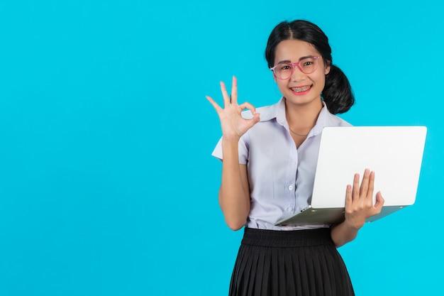 Азиатская девушка студента держа ее тетрадь на сини. Бесплатные Фотографии