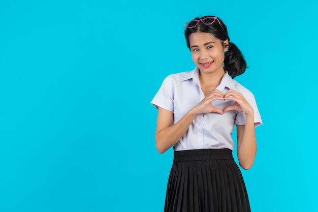 アジアの女子学生が青のさまざまな位置でポーズします。 無料写真