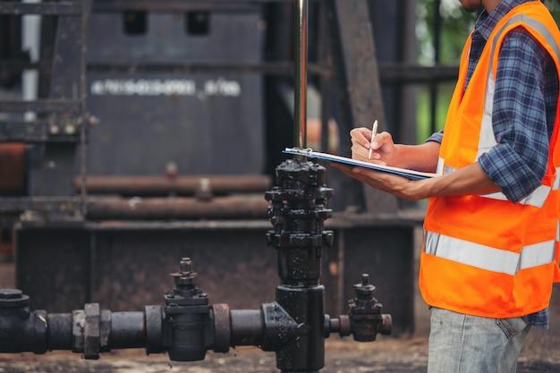 作業用オイルポンプの横に立って確認する労働者。 無料写真