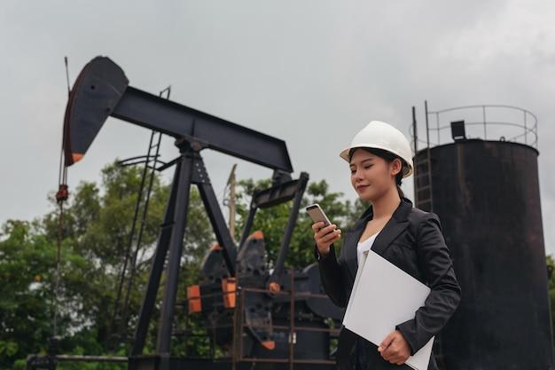 空の作業油ポンプの横に立っている女性エンジニア。 無料写真