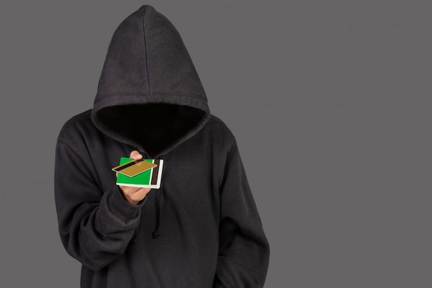 Хакер несет золотую кредитную карту и банковскую книжку Бесплатные Фотографии