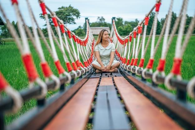 木製の橋の上に喜んで座っている女性 無料写真