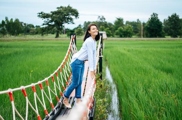 晴れた日に緑の牧草地の木製の橋で幸せな女 無料写真