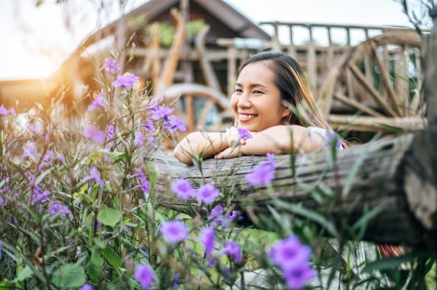 女性はフラワーガーデンに喜んで座って、木製のフェンスに向かって手を置いた 無料写真