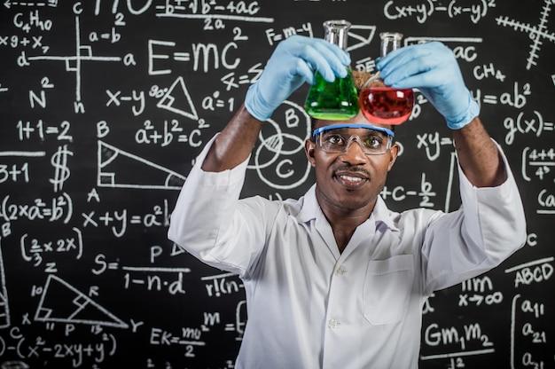 科学者は実験室でガラス中の緑と赤の化学物質を見る 無料写真
