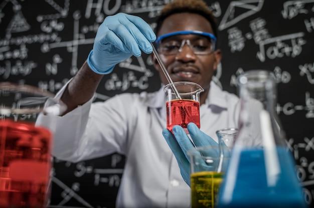 Ученые смешивают красные химикаты в стакане в лаборатории. Бесплатные Фотографии