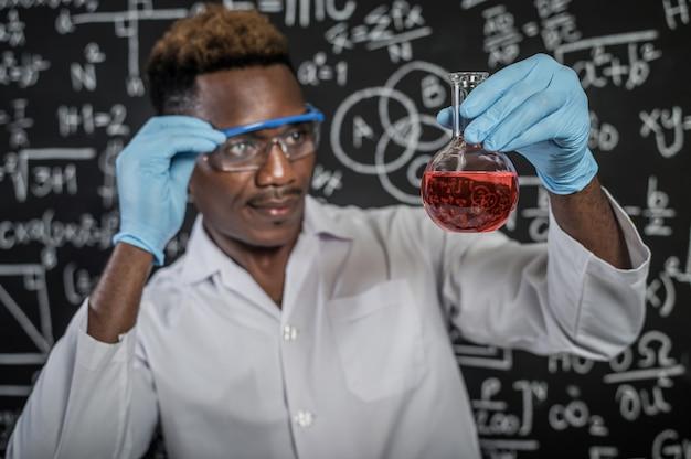 科学者は実験室でガラス中の赤い化学物質を見て、ガラスを手で処理します 無料写真