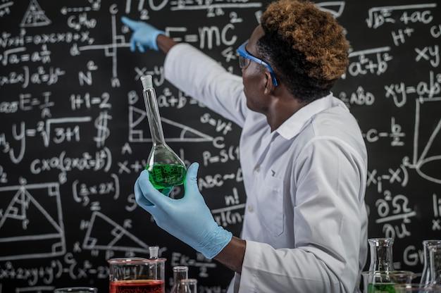 Ученые носят очки с зелеными химикатами и указывают на формулу на доске Бесплатные Фотографии