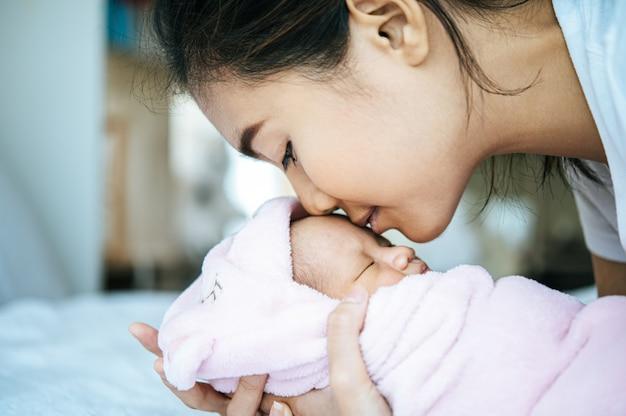 生まれたばかりの赤ちゃんは母親の腕の中で眠り、赤ちゃんの額に香りがする 無料写真