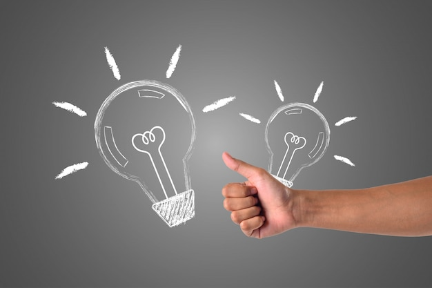 ランプを保持している手は、白いチョークで描かれたコンセプトを描くもう一方の手に送られます。 無料写真