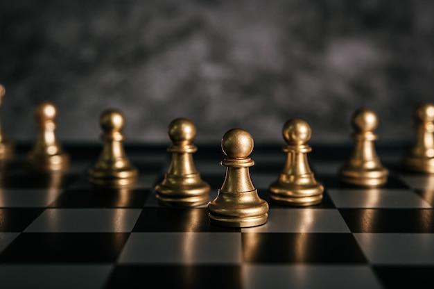 ビジネスメタファーリーダーシップコンセプトのチェスボードゲームでゴールドチェス 無料写真