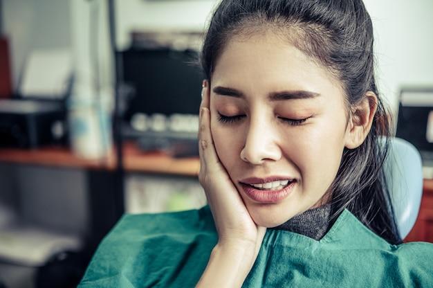 その女性は歯痛で、頬に手を触れていました。 無料写真