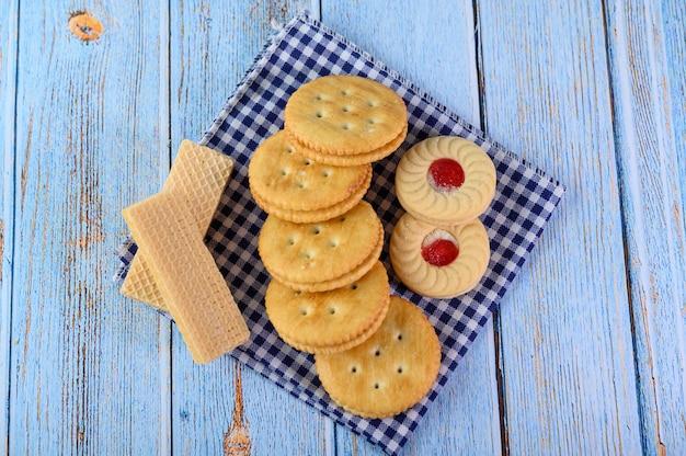 多くのクッキーは生地に置かれ、木製のテーブルに置かれます。 無料写真