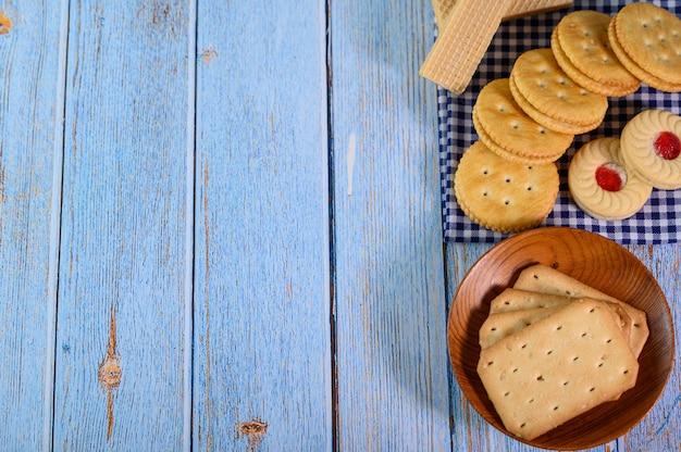 プレートにさまざまな種類のクッキーを積み重ね、木製のテーブルに置きます。 無料写真